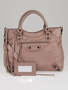 This gorgeous Balenciaga Parme Lambskin Leather Velo Bag has a chic shape that is made of distressed dusty pink lambskin with incredible Classic studded hardware and tassel details. It also has a detachable long shoulder strap to wear this bag as a crossbody. A great bag for any stylish fashionista on-the-go. Current retail price is $1835.
