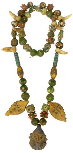 "Multicolored and decorative circular and tubular fused glass beads restrung on a necklace setting. With six fang-like beads and three face pendants. 500-300 BC (28"")"