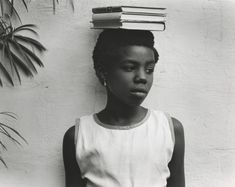 Anna Attinga Frafra rests three books comfortably on her head.  The photographer Paul Strand's 1960's Portrait of Ghana.