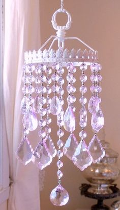 "This gorgeous Suncatcher has been made with a Crown-like ornate lamp part. It hangs by a delicate chain with a little ""s"" hook at the top and has been painted antique white. It has been adorned with loads of sparkly crystal teardrops and fancy-cut French pendants, hanging from multifaceted octagon crystal chains. http://www.lavenderfieldsonline.com/Sparkly-Pink-Crystal-Crown-SunCatcher_p_5505.html"