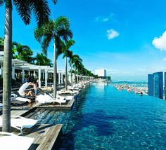 Marina Bay Sands, Singapore At a first glance, this rooftop infinity pool might seem scary, but it is actually hanging over a lower platform of the hotel. It is long and offers an amazing view of the city of Singapore. Sands Hotel Singapore, Visit Singapore, Singapore City, Singapore Travel, Hotel Swimming Pool, Hotel Pool, Singapore Swimming, Hotel Marina Bay Sands, Temples