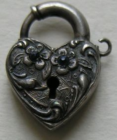 "This fun vintage (circa 1940) heart lock is one that can be a bit hard to find. The heart features two blue pastes set in flowers. The heart lock measures 11/16ths of an inch by 1/2 of an inch. The heart lock is in good working order and has a loop on which to attach a key if you have a spare. The back is marked sterling and is nice engraved with the letters ""W. J. V."" Condition is very good."