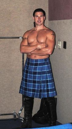 Buffed shirtless hunk wearing blue kilt and black leather boots
