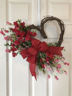 ADORABLE VALENTINE HEART SHAPED WREATH. Grapevine wreath accented with Greenery, Pink Wildflowers and a Burlap/Faux Burlap bow, burlaps ribbons vary slightly . Wreath is approximately 15 wide and 17 long. Last picture shows wreath with red accent flowers and a red bow. Available in Purple