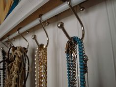 I'm not sure where to do this, but it's an excellent idea...hang a tension rod, hang shower curtain hooks from it...and you have a perfect place to hang your necklaces!