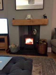 Wood burner stove fire with black slate hearth and solid oak beam mantle piece