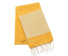 "Luxury mustard Lurex fouta beach towel with a wide band of elegant silver stripes on each end and signature white fringe. 78"" x 39"" 100% natural cotton imported from Tunisia."