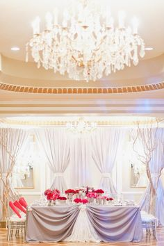 Pink and red floral centerpieces pop dramatically against neutral linens