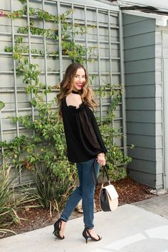Black cold shoulder blouse, denim, and a pair of scalloped heels.