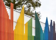 A rainbow-coloured facade shaped like a row of houses fronts this school dining hall in southeast England
