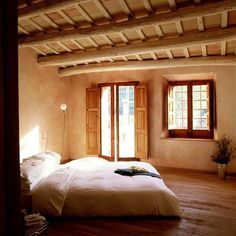 From Build Naturally with Sigi Koko; peeled log beams, strawbale walls with deep window openings, clay plaster.