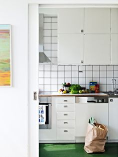 I absolutely adore the retro kitchen cabinets! Fresh, green floor and white tiles above the counter.