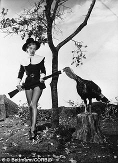 Naughty Puritan: Wearing a costume that is half-Pilgrim, half-showgirl, Marilyn Monroe seems to have little desire to hunt turkey after finding this gobbler in a 1950 photo shoot