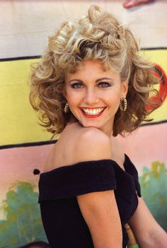 """Much of the charm of """"Grease"""" revolves around Sandy's transition from wholesome to baaaaad to win John Travolta's heart.  The fashion and style of Olivia Newton-John, from simple blonde flip with bangs and white eyelet, full-skirted dresses to her signature look of hoop earrings, black off-the shoulder  top, skin-tight lycra ankle pants, big buckle, and red heels is so fun.  Not to mention that big, curly hair!!  She's the one that we want...."""