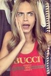"""The Brian Lichtenberg Bucci Tank Top in Red worn by Cara Delevingne, is the epitome of high-fashion streetwear. This super soft cotton tank features """"BUCCI"""" emblazoned on the front with red and green accents beneath the text. The deep cut sleeves complete this look."""