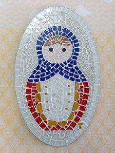 Quadro de Mosaico Matrioshka Nina. <br>Design exclusivo, feito pela mosaicista Tainah Neves. <br> <br>Mosaico feito à mão com Pastilhas de Porcelana, Pastilhas Cristal, Pastilhas de Vidro e Pastilhas Especiais Importadas. <br> <br> <br> <br>Dimensões: 33 cm x 20 cm, espessura 1,3 cm.