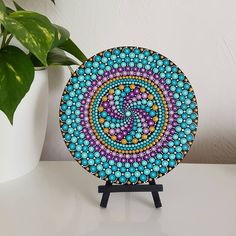 This hand-painted mandala dot art is created on a round 18cm wood slice from the French Riviera. It is painted all black, with detailing in a mix of colours; turquoise, aqua, purple, light purple, gold and white finished with a lighter shade of each colour in every dot. This art will