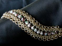 Here is a handmade, original design chain maille bracelet made by yours truly. The chain maille is crafted of jewelers brass & the beads are enameled cloisonne. The beads are not strung together, instead they are each individually woven into the actual chain maille. The bracelet is very fluid & f...