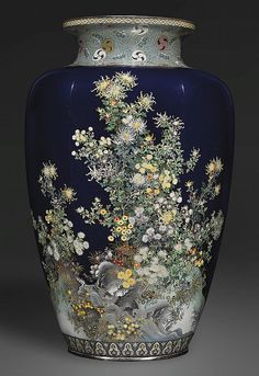 An Impressive Large Scale Cloisonné Vase The mark of Inaba Nanaho, Meiji Period (late 19th century) Of rare rounded hexagonal form, worked in silver wire and various coloured cloisonné enamels on a midnight blue ground with gold specks, decorated with a profusion of chrysanthemums, spider chrysanthemums and daisies on rocks beside a stream, beneath a finely detailed design to the neck. Silver rims, 61.6cm high.  Christies 2011 - unsold.