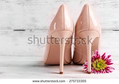 Female shoes with flower on wooden background