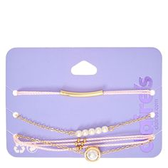 Add a romantic touch to your style with this set of bracelets. Pearls, gold and pink combine to create the ultimate feminine chic look. Includes one of each: pink yarn with gold bar, gold chain with white pearls, triple pink yarn band, and gold chain with single pearl.