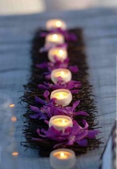 Un mantel de arpillera azul. Caminos de mesa para bodas en arpillera y velas rodeadas con pétalos de flores. Resultado: una decoración de boda romántica en Florianópolis.
