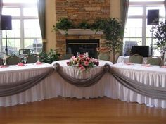 1 round table and 2 banquet for the bridal party table. Love the table skirts and gray drape on front. No angle though, want them lined up straight.