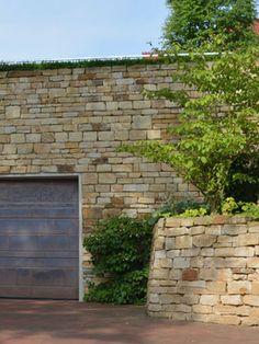 Natursteinmauern aus Sandstein fangen bei der Anlage dieses pflegeleichten Gartens den Höhenunterschied zur Straße auf und rahmen die Einfahrt der Tiefgarage des Hauses ein. Garage Doors, Patio, Outdoor Decor, Home Decor, Underground Garage, Low Maintenance Garden, Drive Way, Bielefeld, Birch