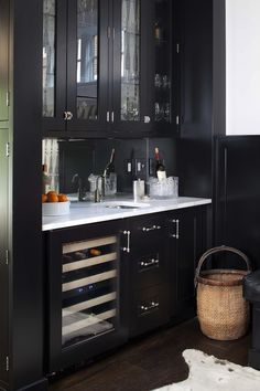 Stunning black butler's pantry design with glass-front upper cabinets and black lower cabinets with glass-front wine cooler paired with carrara marble countertops and mirrored backsplash.