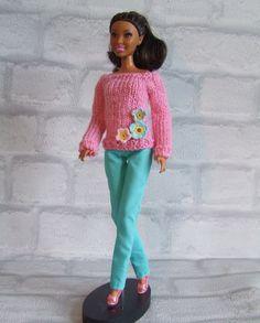 Roze gebreide trui met kleine gehaakte bloemetjes op aqua-kleurige lange broek…
