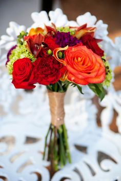 Jewel tones-- green hydrangea, red roses, red and deep purple carnations, green hypericum, calla lilies, red/yellow roses