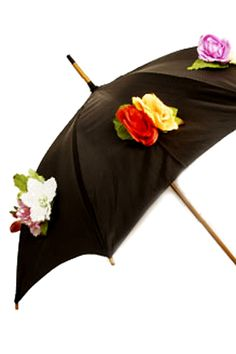 """FLOWER UMBRELLA      Details: Measures 48"""" (122cms) in diameter when opened  * Handle length 7.1"""" (18cms)  * Cover length 14.2"""" (36cms)    Still keeping that spring summer feeling alive... Spreading the vibe with this gorgous high quality umbrella.     A sumptuous twist on the traditional English Umbrella, black but with delightful plastic flower detailing that makes it stand out from the crowd. Solid polished wood shaft construction with """"Nancy Pop"""" sheath to keep it covered. Price: £45"""