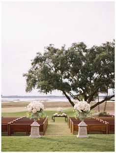 Outdoor wedding ceremony decor with natural wooden pews and white flowers in tall urns overlooking The River Course at the Kiawah Island Club in SC. Florals and design by Bella Flora, pew rental from Calder Clark, image by Landon Jacob.