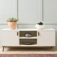 Another classically shaped buffet, our Fonso is fully wrapped in our textured faux Belgian linen. Available in two heights, this credenza features brass legs, and double doors with rectangular hardware for a modern look and easy opening. A narrow, clean piece for any dining or living area. Adjustable shelves and cord management cutouts are perfect for stowing media equipment.   Finish: White Faux Belgian Linen (Shown), Brown Faux Belgian Linen