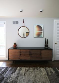 The sleek midcentury modern console brings out the rugged texture of the gray area rug. Sooo pretty!!