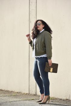 Girl With Curves blogger Tanesha Awasthi wears a satin bomber jacket, peplum top, skinny jeans, olive green pumps and vintage Louis Vuitton clutch bag.