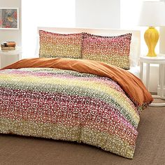 Fiesta Stripe by City Scene bedding features an ombre stripe with a trellis print. Ombre stripe has yellow, orange, red, and green colors with an underlying trellis design over a white ground. On the reverse is a tonal trellis design in spice orange. Shams coordinate perfectly with the duvet and comforter. Wrap yourself in a new 100% cotton City Scene bedding set today. Starting at $59.99 #bedding #comforter #cityscene #beddingstyle #homedecor