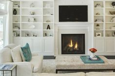 Chic, transitional living room features a sleek white fireplace and a flatscreen TV flanked by floor to ceiling built-in shelves and cabinets.