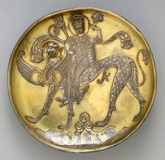Plate   Date:   probably 8th century   Geography:   Iran   Medium:   Silver; gilded, chased, and engraved, with applied elements   Dimensions:   H. 1 9/16 in. (4.0 cm) Diam. 8 1/8 in. (20.6 cm)   Description   Like Sasanian examples, this plate depicts a female figure riding a fantastic winged beast with a feline head, feathered body, and canine legs. Her figure is unnaturalistically twisted, a quality seen on late seventh and early eighth century Central Asian wall paintings from Panjikent.