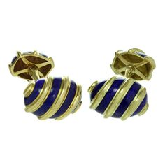 """Tiffany & Co. Schlumberger Blue Enamel Yellow Gold Olive Cufflinks. These modern Tiffany & Co. cufflinks were designed by Schlumberger and feature an olive-shaped ridged design made in 18k yellow gold and accented with blue enamel. Classic and handsome elegance. Measurements: 0.43"""" (11mm) x 0.62"""" (16mm) front, 0.35"""" (9mm) x 0.51"""" (13mm) back ."""