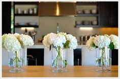 Beautiful hydrangias in glass hurricane lamps