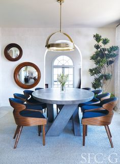 A modern dining room designed in a blue color palette with a custom Bausman & Company table and a stunning John Liston Halo pendant.  via @cottagesgardens