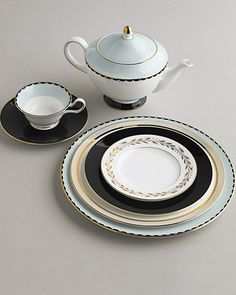 Dark Glamour: Black adds visual weight to china with ethereal, classical details. All by Wedgwood, except for top plate on stack by Marc Jacobs and gold striped dinner plate by the Martha Stewart Collection with Wedgwood.