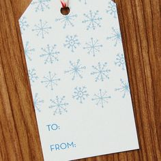 Spruce up your holiday gifts with this patterned gift tag. This tag features a hand-drawn pattern of blue-gray snowflakes. Full pattern coverage on the back of the tag. Red and white twine is included