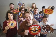 Bill Gardner, center, and his staff at Gardner Design hold up renderings of some of the stickers they designed to promote civic pride in Wichita.