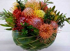 Tropical Leucospermum tablecenter bowl arrangement in Coconut Leaf woven basket