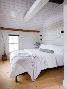 In the upstairs master bedroom, the couple also installed shiplap to accentuate the lofty ceiling. The pendant is Schoolhouse'sLuna Pendant Cord with 12″ Shade; $239.