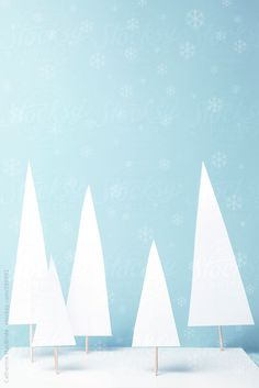 Tall paper pine trees made of white paper stand on skewers against an icy blue background scattered with snowflakes