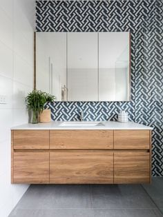 Heres how to use a feature tile in a bathroom - create a stunning feature wall behind the vanity, add a wall hung custom made timber vanity and be smart with storage by adding face-level cabinetry