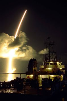 Nighttime launch of rocket with Cassini orbiter aboard seen from water with ship in foreground